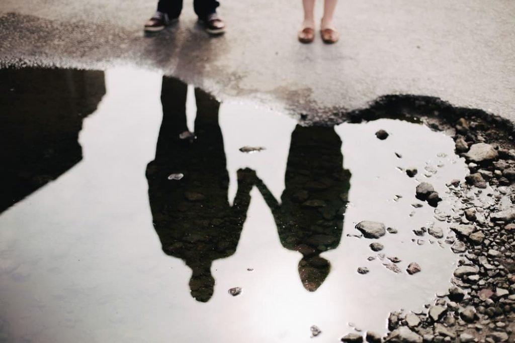Reflet d'un couple se tenant par la main. | Source : Unsplash