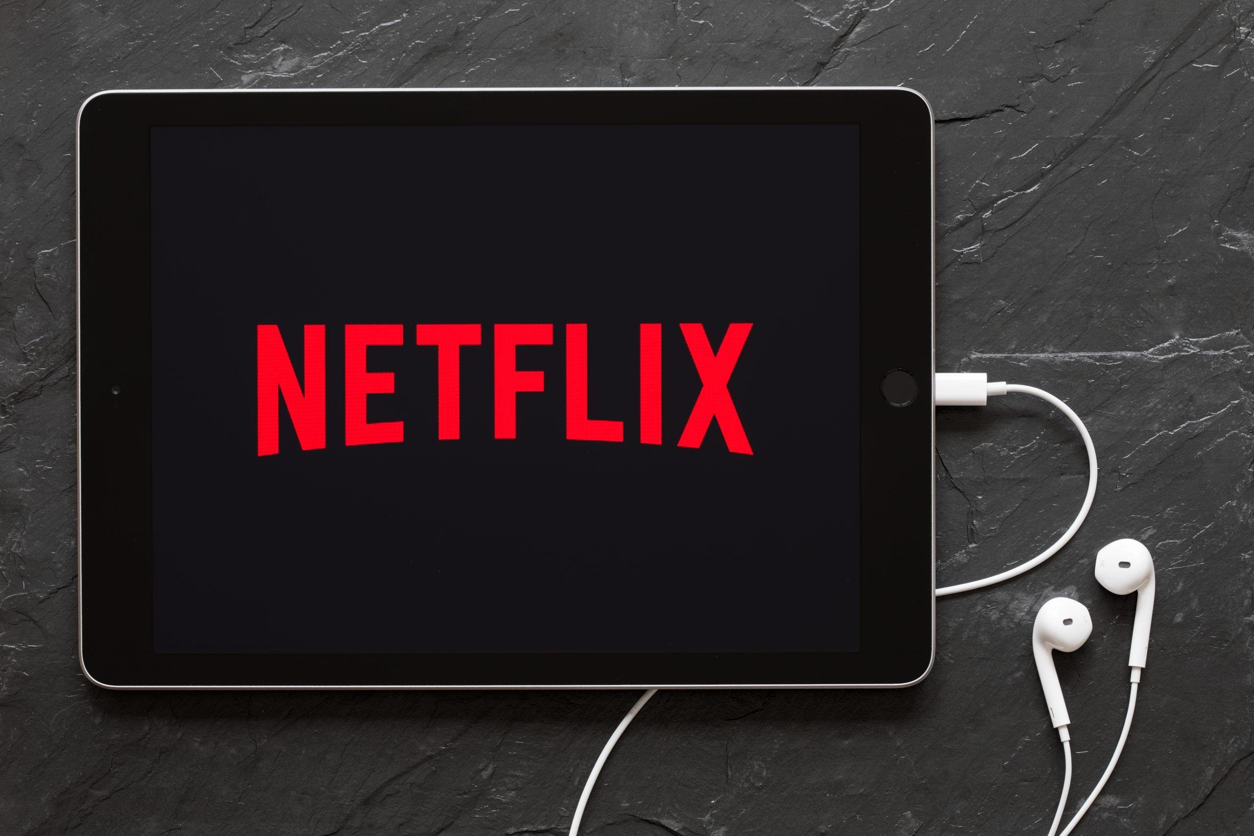 Écouteurs connectés à l'iPad affichant le logo Netflix sur l'écran. | Photo : Shutterstock