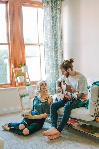 Un homme jouant de la guitare pour sa copine. | Photo : Pixabay