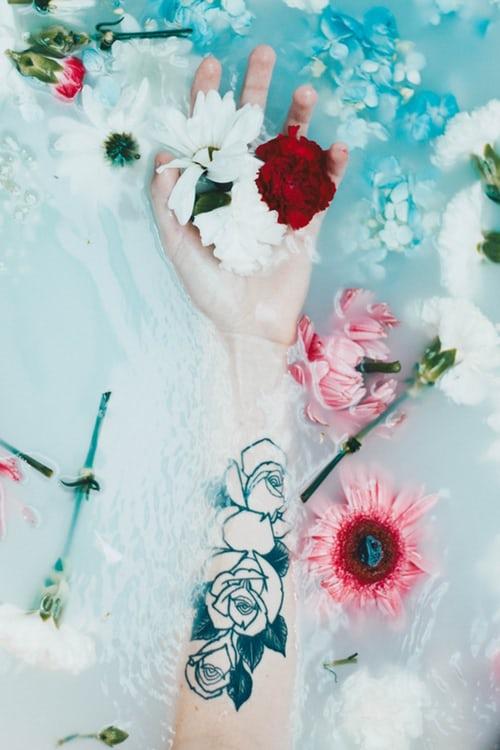 Un bras plongé dans l'eau avec des pétales de rose. | Photo : Unsplash