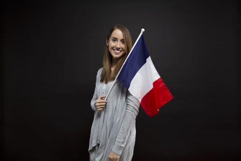 Femme tenant un drapeau Français. Source : Unsplash
